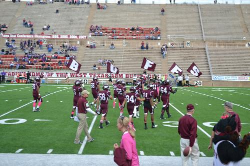 Maroon Platoon charge the field with flags as the football players enter. Photo by Alex Montoya.