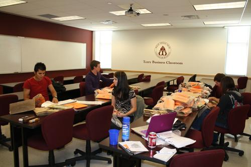 Project leader Betheny Wilcox (center) helps SIFE stuff goodie bags. Photo by Alex Montoya.
