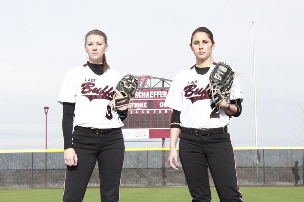 Alyssa Lemos (left) and Mercedes Garcia pose in front of the scoreboard. Photo by Johnny Story and courtesy of WTAMU Athletics.