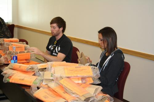 Mason Wright (junior) and Shelbi Cooper bag up goodies to hand out. Photo by Alex Montoya.