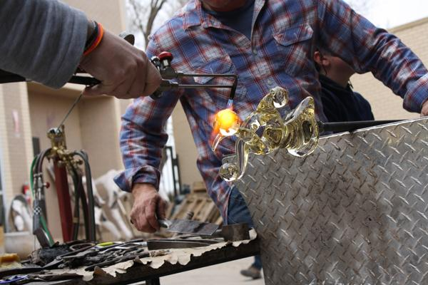 Clayton Spaulding assisting Rob Stern with a blowtorch in glass blowing class.