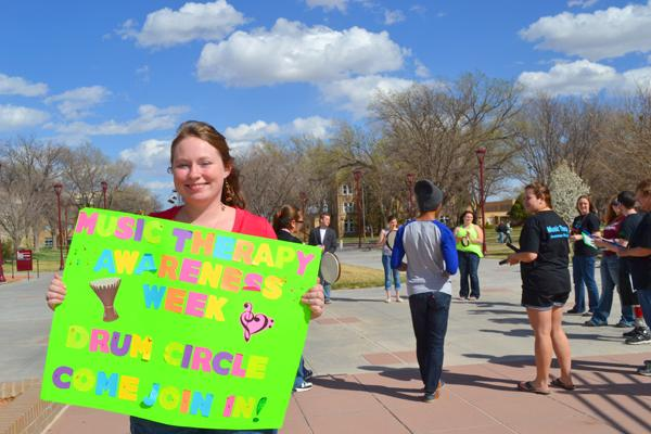 Vice President Meghan Garner holds up a sign to invite people to join Music Therapy Awareness Week.