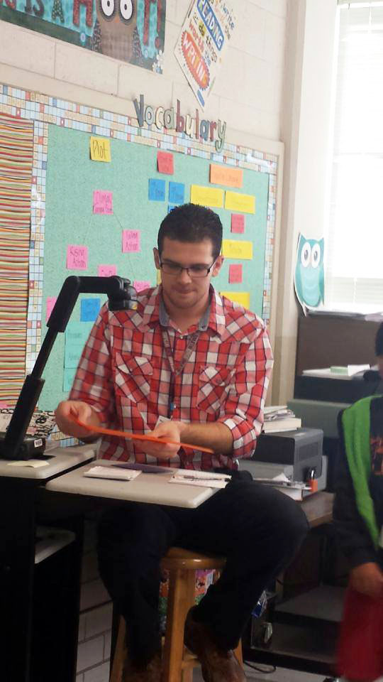 J.D. Thompson uses a document camera, which projects  what he is holding onto the screen so students can see.